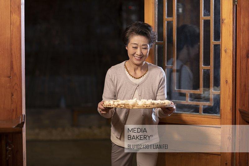 Happy senior woman holding dumplings