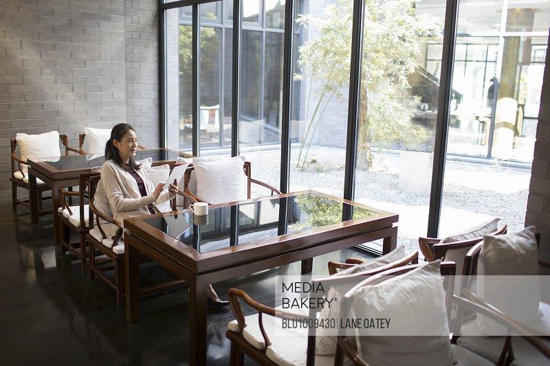 Elegance mature woman using digital tablet in caf�