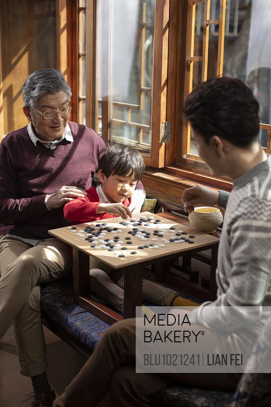 Happy family playing the game of go