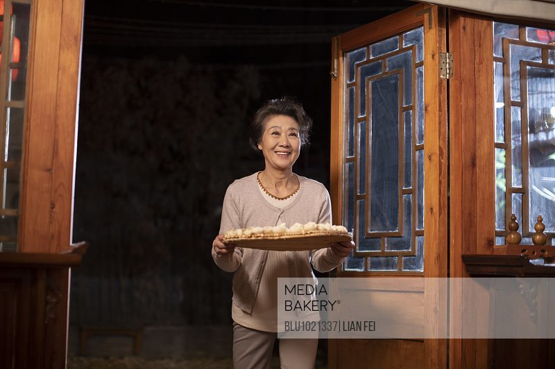 Happy senior woman holding dumplings