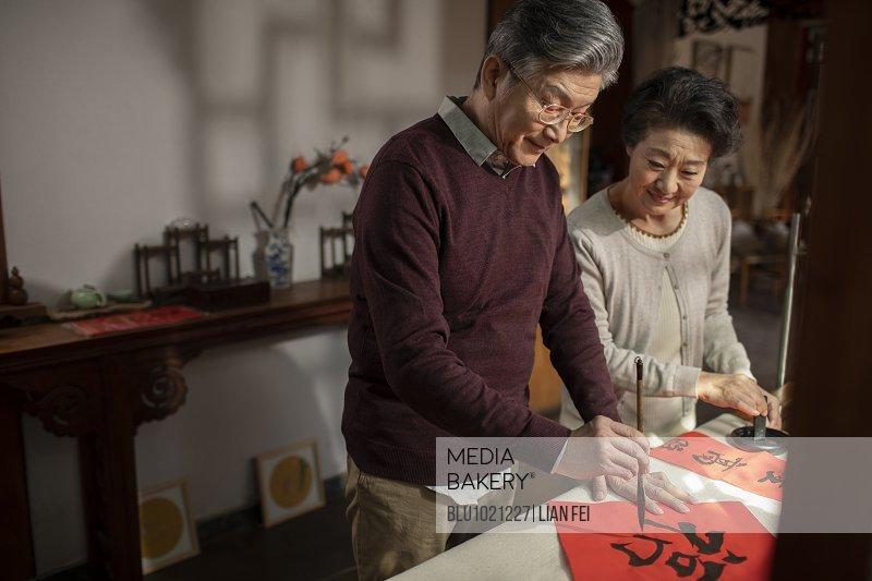 Happy senior couple writing calligraphy on couplets