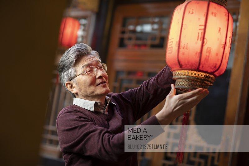 Happy senior man and Chinese lantern