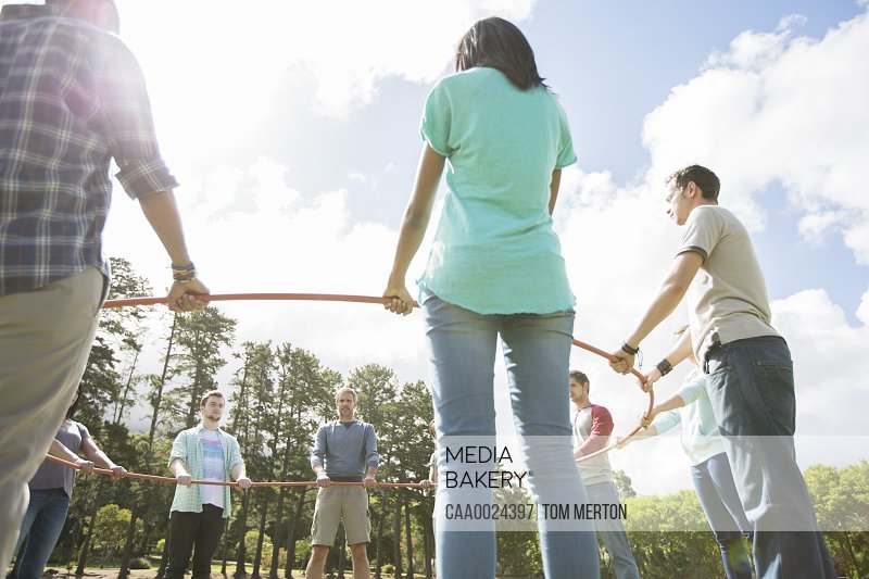 Team forming connecting circle around plastic hoop