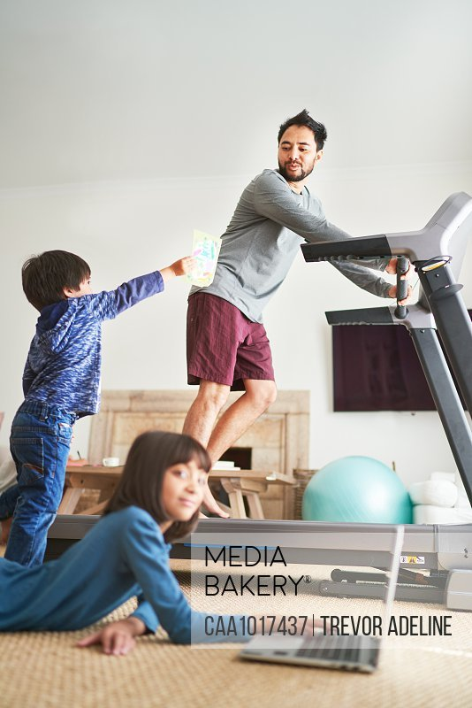 Kids in living room with father on treadmill