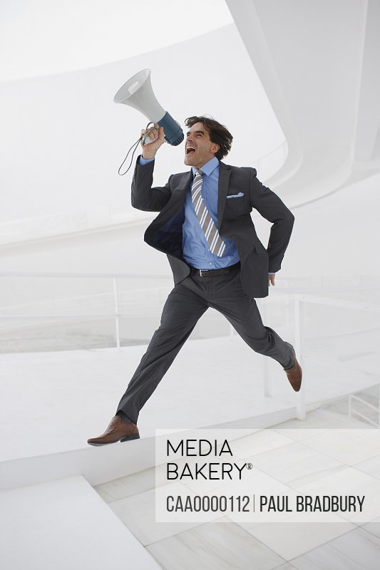 Leaping businessman with bullhorn