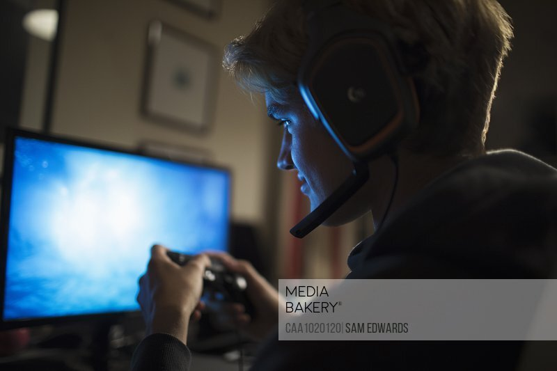Teenage boy with headset playing video game at computer in dark room