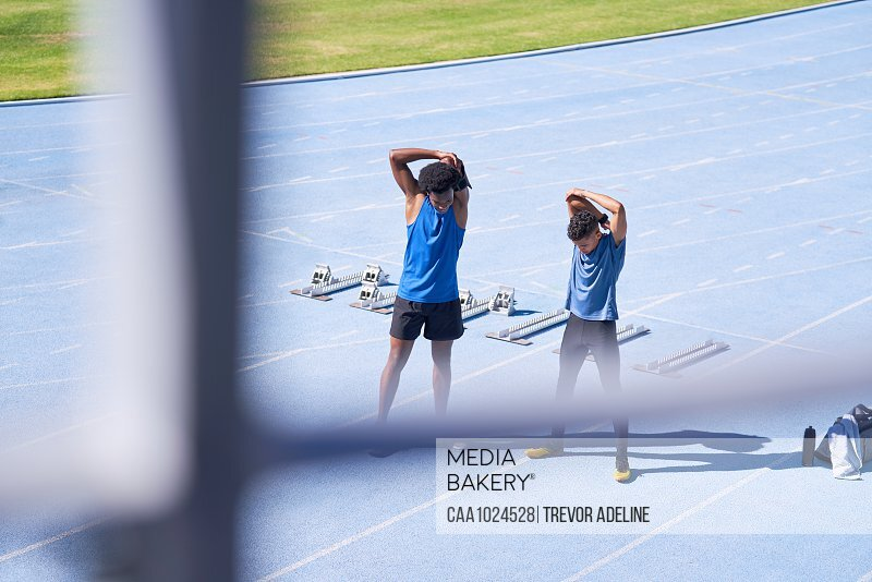 Male runners stretching on sunny blue sports track