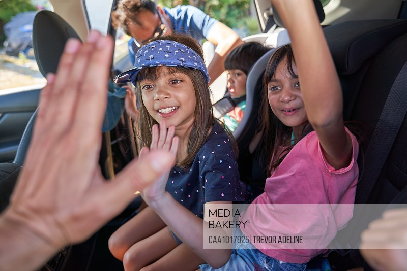 Happy kids high-fiving in back seat of car