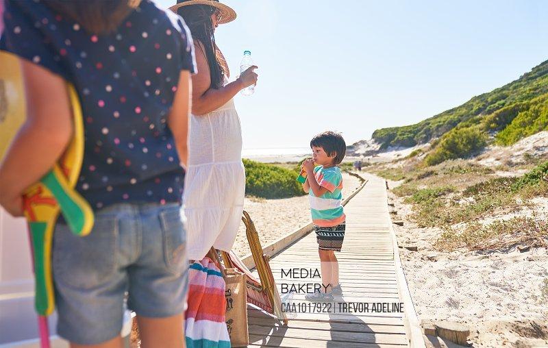 Family drinking water on sunny beach boardwalk