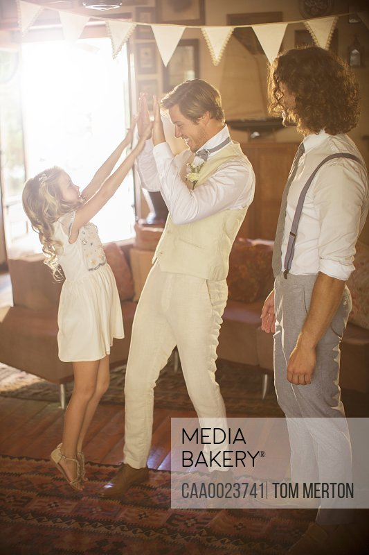 Groom and bridesmaid high fiving in domestic room