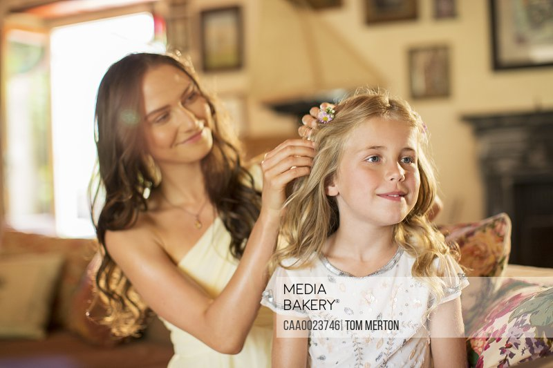 Bridesmaid helping girl with hairstyle in domestic room