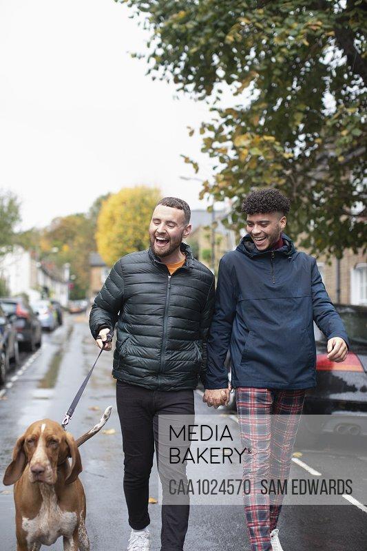 Happy gay male couple walking dog on wet urban street