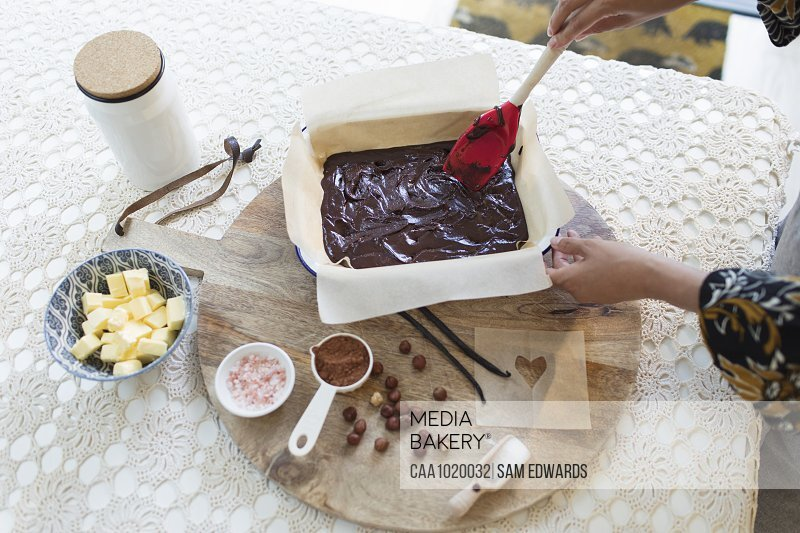 Woman baking chocolate cake at dining table