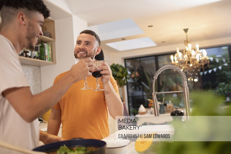 Happy gay male couple drinking wine and cooking in kitchen