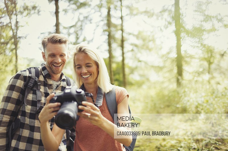 Smiling couple hiking viewing digital SLR camera in woods