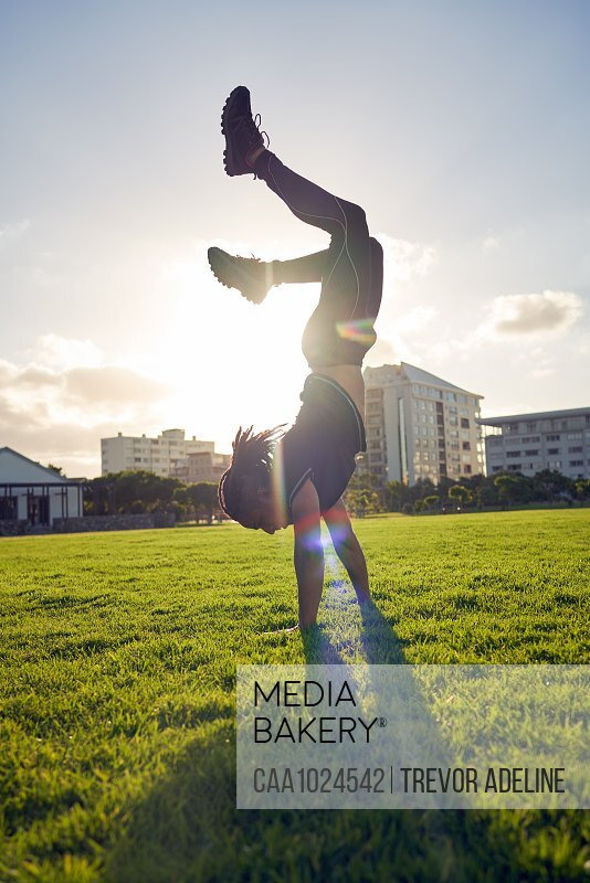 Carefree young man doing handstand in sunny park grass