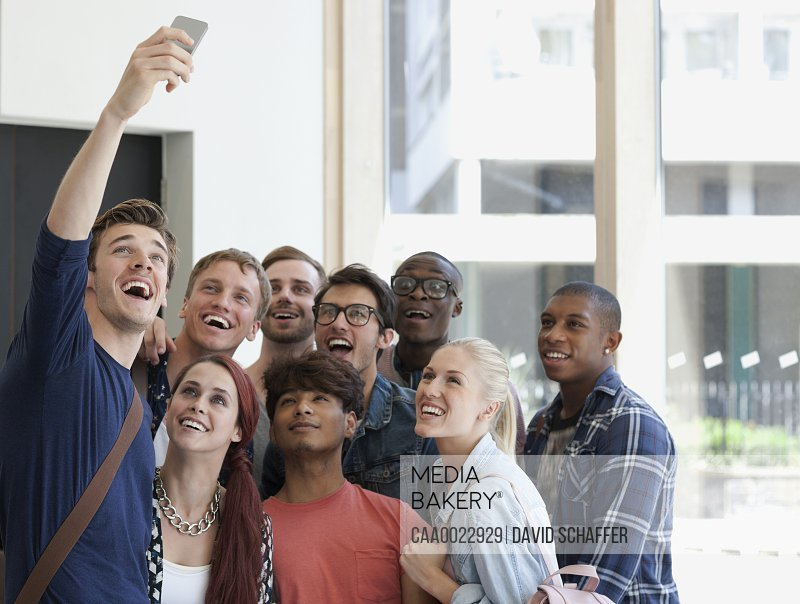 Group of laughing students taking selfie on corridor with large window in background