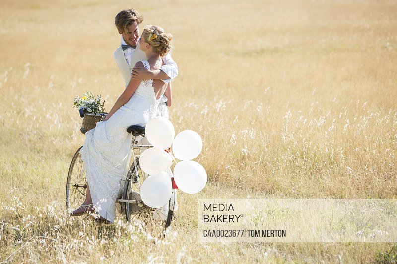 Bride and bridegroom riding bike with balloons attached