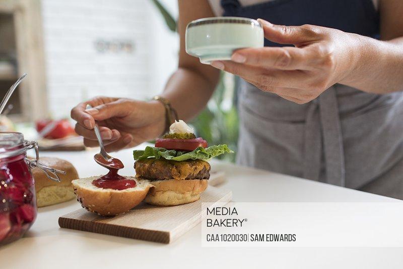 Close up woman spreading ketchup on cheeseburger bun