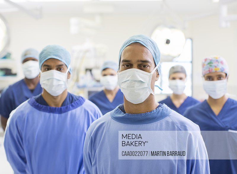 Group portrait of team of masked surgeons in hospital