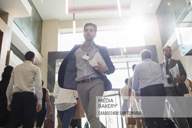 Men holding documents and running in office corridor