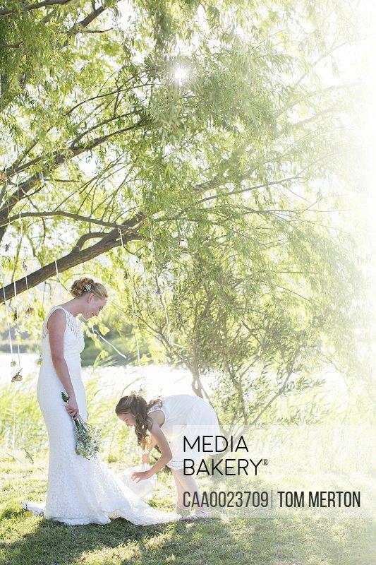 Bride and bridesmaid standing in domestic garden during wedding reception