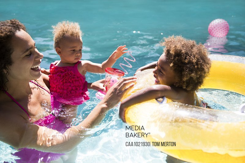 Mother and daughters playing in sunny summer swimming pool
