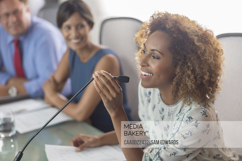 Beautiful woman sitting at conference table talking into microphone