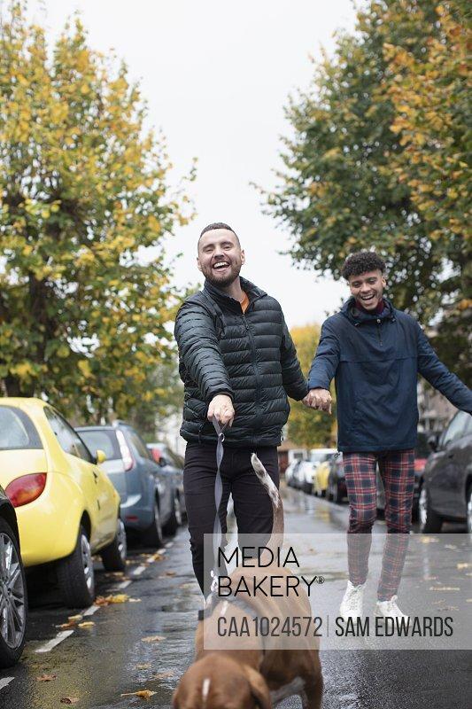 Happy gay male couple walking dog on wet autumn street