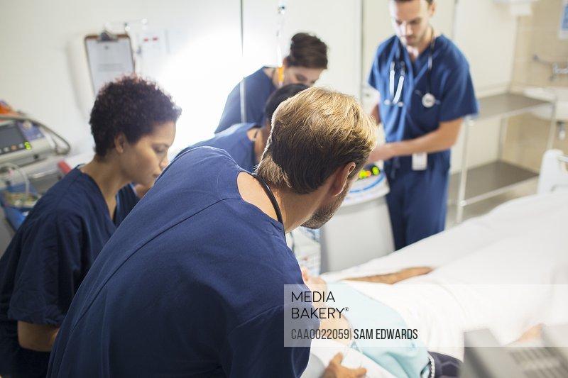 Team of doctors attending patient in hospital