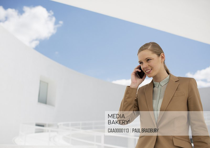 Smiling businesswoman talking on cell phone in courtyard