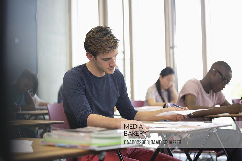University student taking exam students in background writing