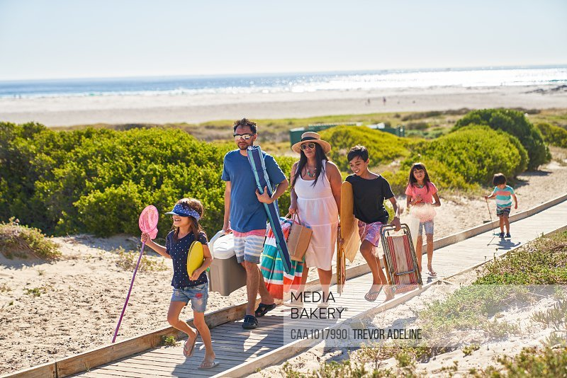 Family carrying chairs and toys on sunny beach boardwalk
