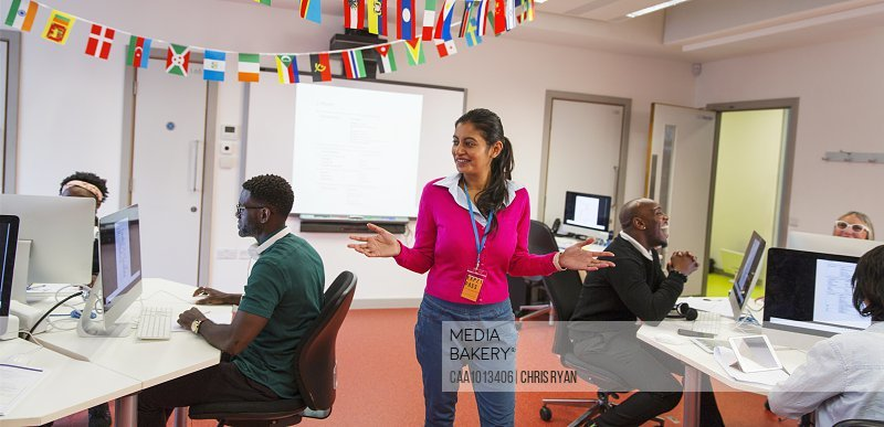 Community college instructor guiding adult students using computers in classroom