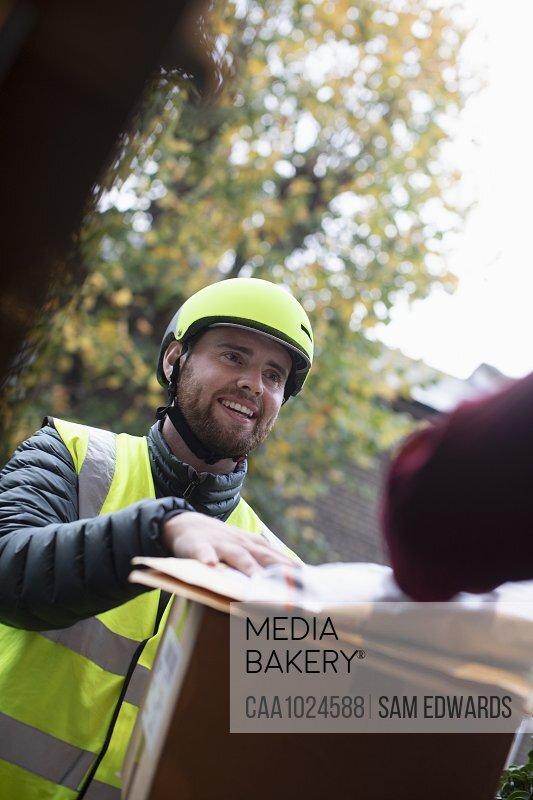 Friendly delivery man in helmet delivering packages at door