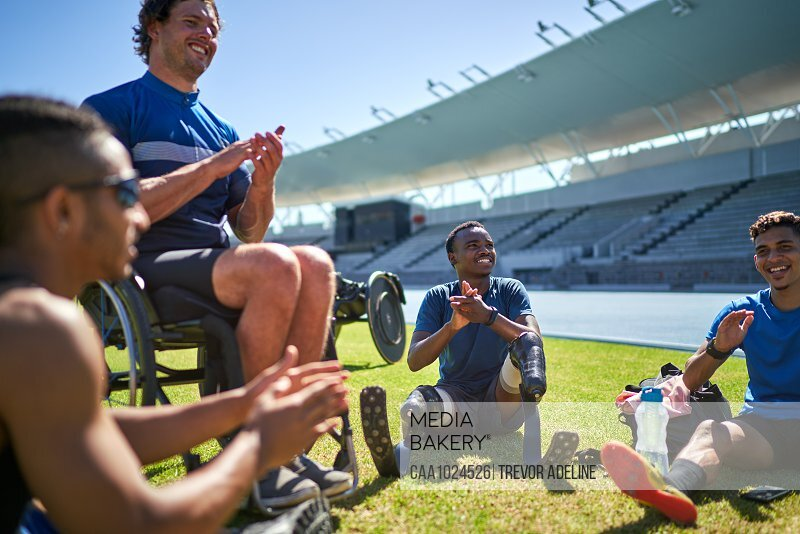 Paraplegic and amputee male athletes clapping on sunny stadium grass