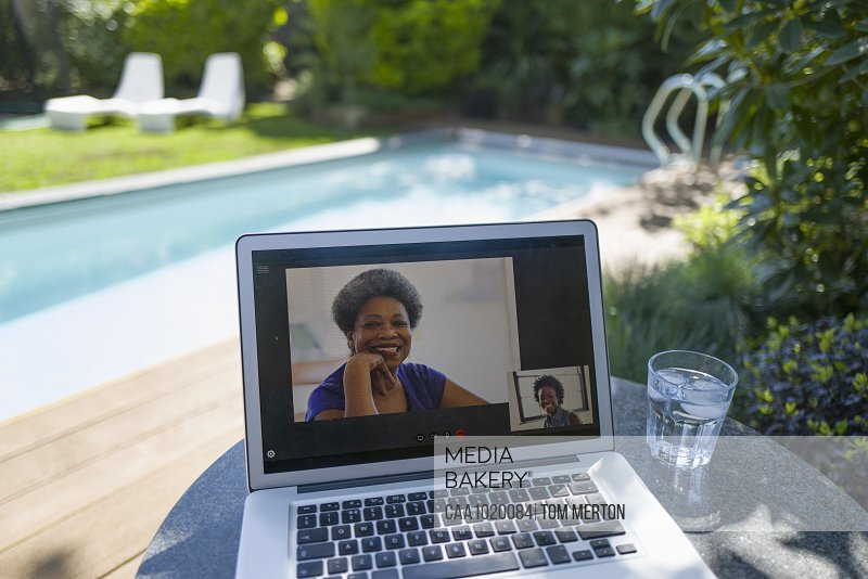 Women video conferencing on laptop screen at sunny poolside