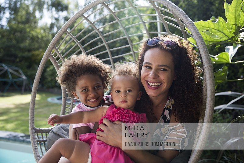 Portrait happy mother and daughters in summer swing chair