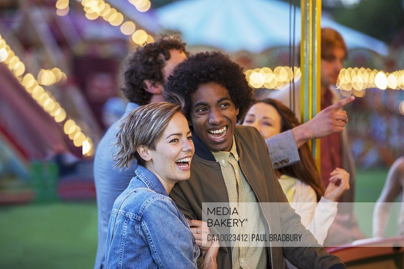 Young multiracial couple having fun in amusement park