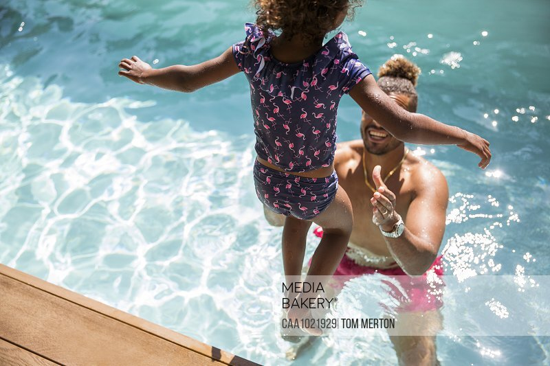 Daughter jumping into arms of father in sunny swimming pool
