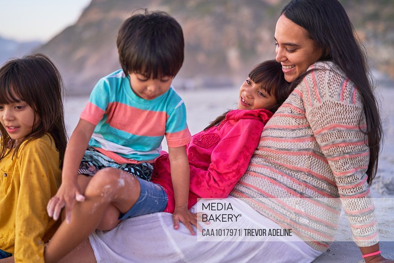 Happy mother and kids relaxing on beach