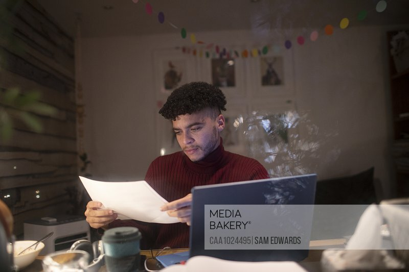 Focused young man with paperwork working late in home office