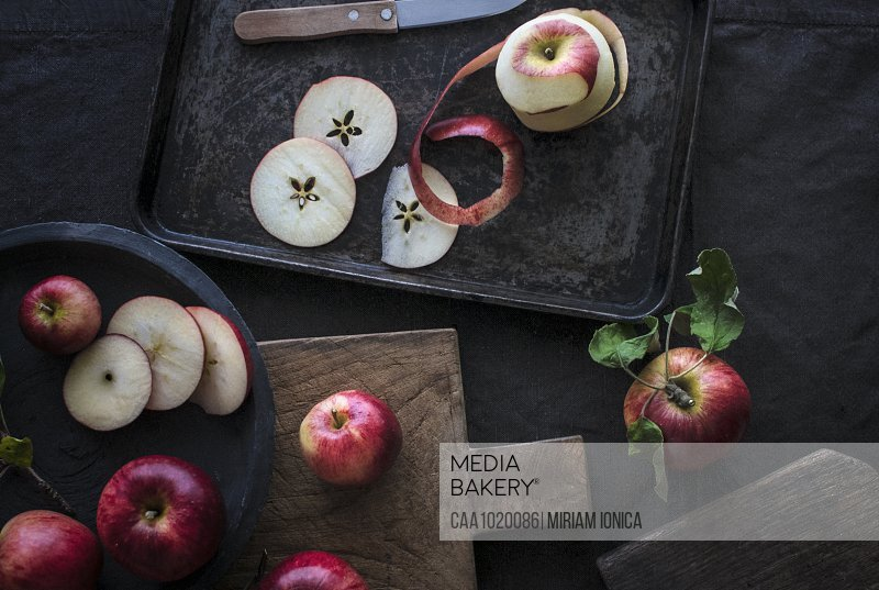 Fresh red apple slices on cutting board and sheet pan