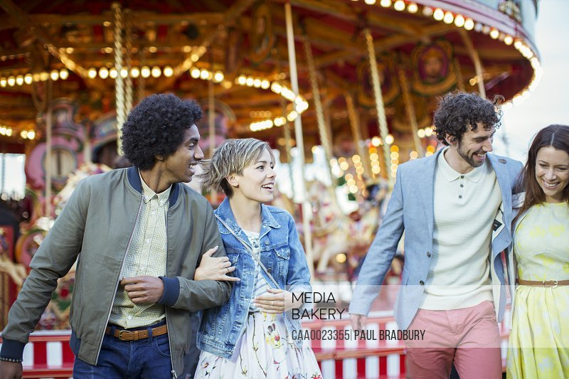 Two couples walking in amusement park and laughing