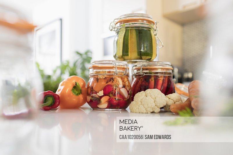 Pickled vegetables in jars on kitchen counter