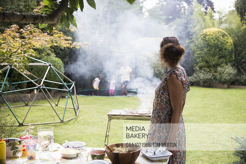 Woman barbecuing and watching family play on backyard trampoline