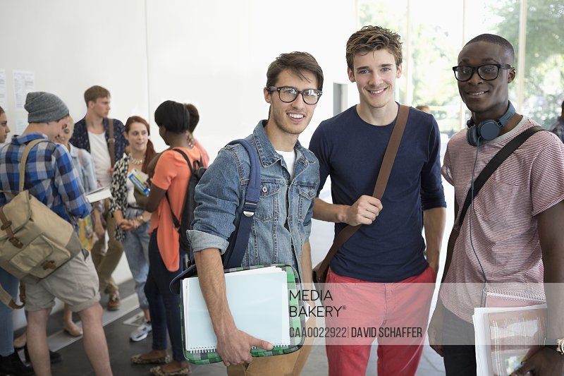 Three smiling male students standing together with other students in background