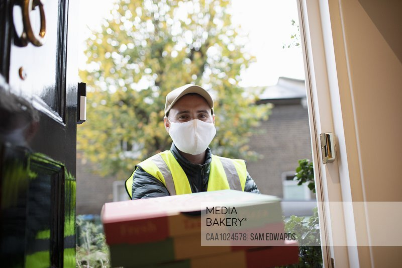 Portrait delivery man in face mask delivering pizza at front door