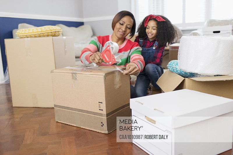 Mother and daughter taping moving boxes, moving house