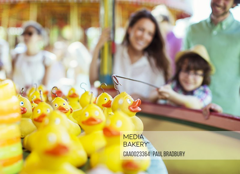 Boy trying to catch rubber duck on fishing game in amusement park